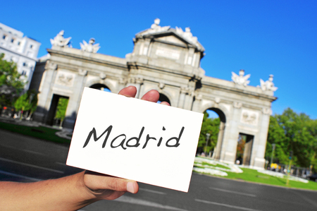 a man holding a signboard with the word Madrid written in it in front of La Puerta de Alcala in Madrid, Spain photo