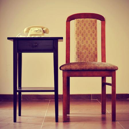 rotary dial telephone: beige viejo tel�fono de disco en una mesa al lado de una silla, con un efecto retro