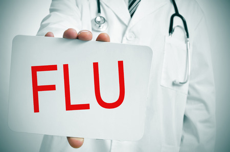 a doctor showing a signboard with the word flu written in it