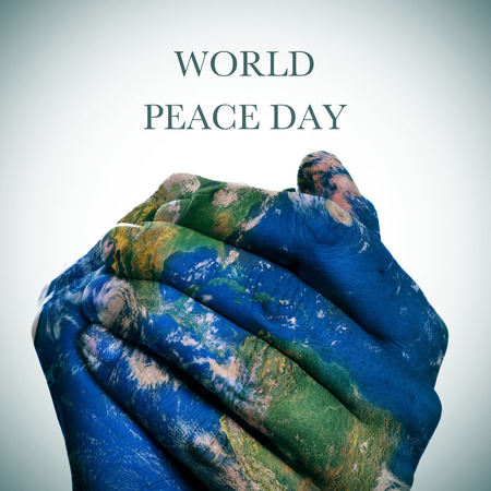 the sentence world peace day  and a world map in man hands forming a globe Stok Fotoğraf