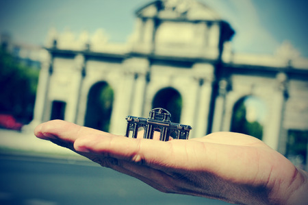 someone holding a reproduction of the popular landmark La Puerta de Alcala with the real  photo