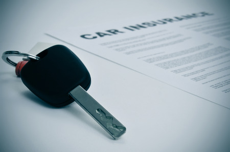 insurance policy: closeup of a car key and a car insurance policy