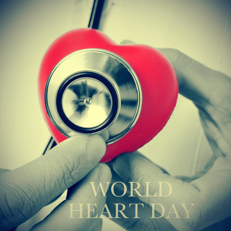 sick day: closeup of a doctor auscultating a red heart with a stethoscope and the text world heart day