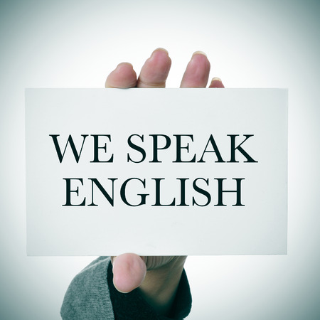 woman hands showing a signboard with the sentence we speak english written in it photo