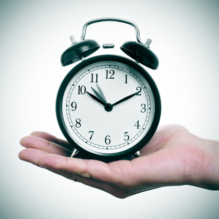 turn back: someone holding an alarm clock adjusting backward one hour at the end of the summer time
