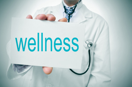 geriatrician: a doctor showing a signboard with the word wellness written in it