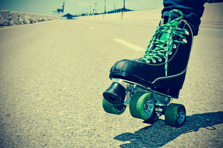 sporting activity: closeup of a young man roller skating on a no traffic road, with a retro effect
