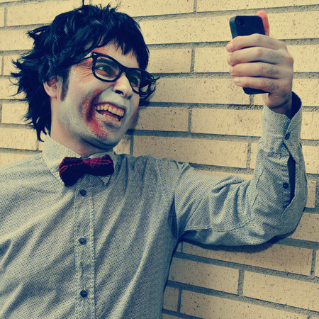 a scary hipster zombie taking a selfie of himself with a smartphone, with a retro effect photo
