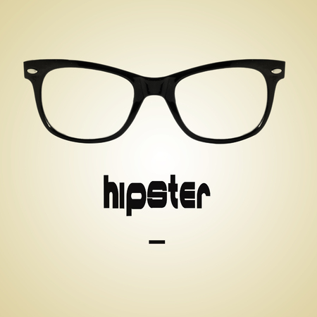 black rimmed: the word hipster and a black plastic rimmed eyeglasses on a beige background with a retro effect