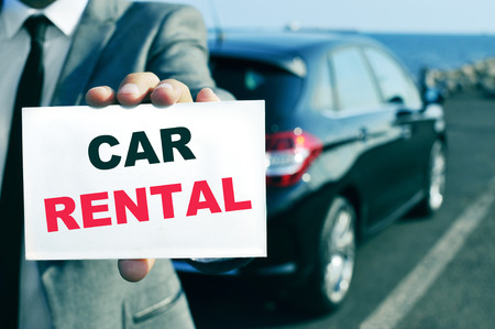 chauffeur: a man in suit holding a signboard with the text car rental written in it and a car in the background
