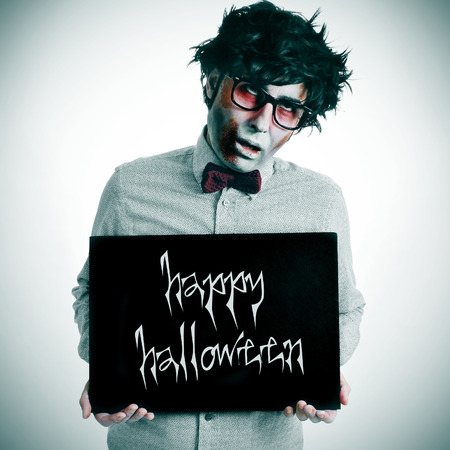 a hipster zombie showing a black signboard with the text happy halloween written in it photo