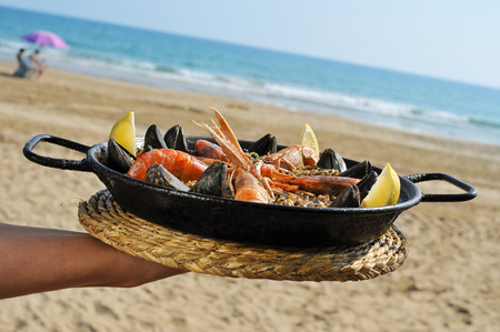 a typical spanish paella with seafood in a paellera, the paella pan, on the beach