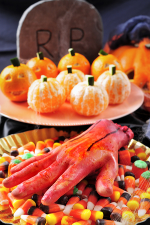amputated: some plates with different Halloween food, such as candies, mandarines as pumpkins, and scary ornaments such as an amputated hand or a grave