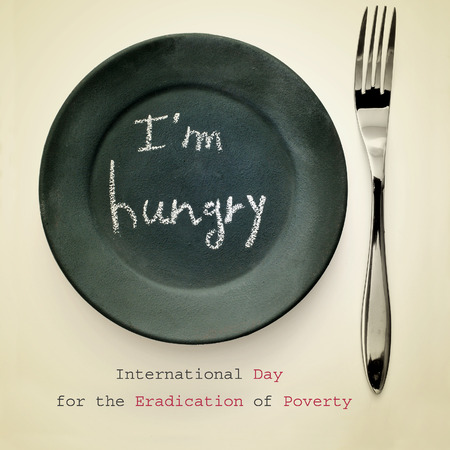indigence: a fork and a plate painted as a chalkboard with the text I am hungry written in it, for the International Day for the Eradication of Poverty