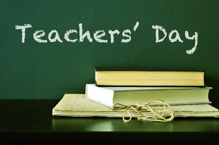the text Teachers Day written with chalk on a green chalkboard and some books on a desk