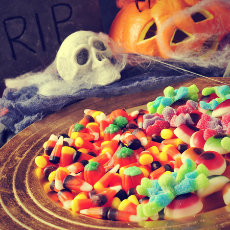 a pile of different Halloween candies with scary ornaments in the background, such a tombstone, a skull, a pumpkin and cobwebs photo