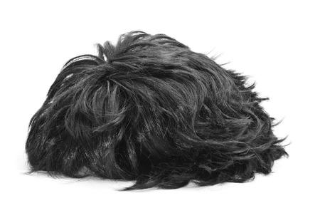 artificial hair: una peluca de pelo negro sobre un fondo blanco Foto de archivo