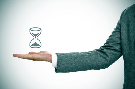 a businessman holding an illustration of an hourglass in his hand Stock Photo