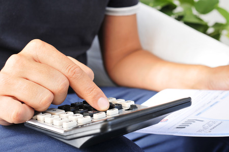Detailní záběr na mladé muže, kontrolu účet, rozpočet nebo mzdy s kalkulačkou