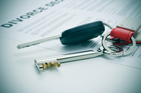 human settlement: a divorce decree document and the keys of a car and a house