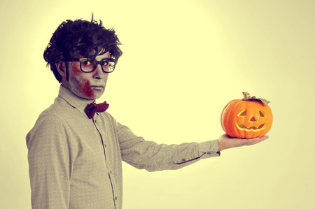 a hipster zombie with a jack-o-lantern in his hand, like Hamlet, with a retro effect photo