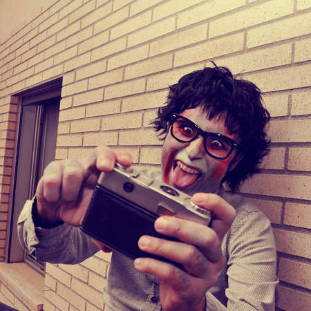 a scary hipster zombie taking a selfie of himself with a vintage camera, with a retro effect photo