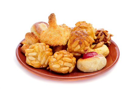 panellets: an earthenware plate with panellets, typical pastries of Catalonia, Spain, eaten in All Saints Day, on a white background Stock Photo