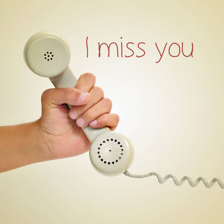 a man hand holding the handset of a telephone and the text I miss you, with a retro effect photo