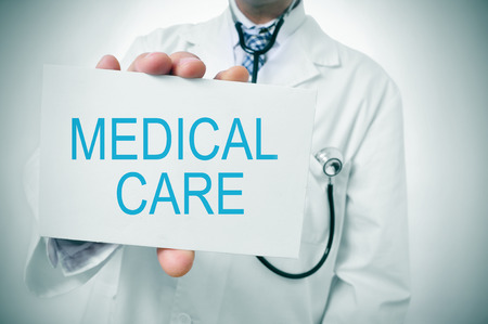geriatrician: a doctor showing a signboard with the text medical care written in it