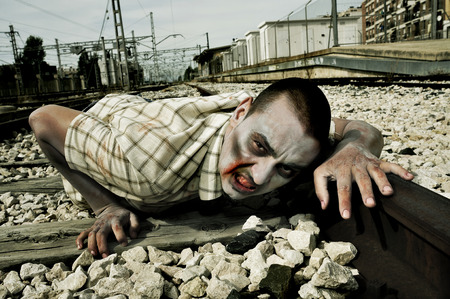 crawl: a scary zombie crawling by the railroad tracks Stock Photo