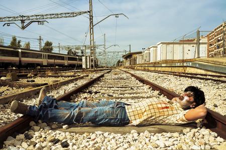 a scary zombie taking a nap at abandoned railroad tracks photo