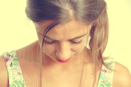 embarrassed: portrait of a young brunette woman looking downwards, with a retro effect Stock Photo