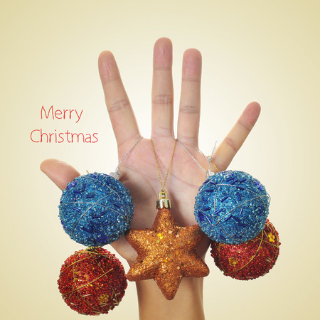 the text merry christmas and a man hand, as a christmas tree, ornamented with christmas balls on a beige background, with a retro effect photo