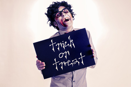 a gap-toothed zombie showing a black signboard with the text trick or treat written in it, with a retro effect photo