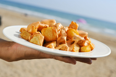 spiced: closeup of a plate with typical spanish patatas bravas, fried potatoes with a hot sauce, on the beach