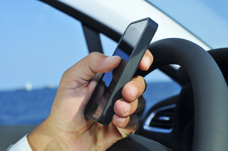 closeup of a man using a smartphone while driving a car photo
