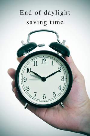 back in an hour: an alarm clock adjusting backward one hour and the text end of daylight saving time
