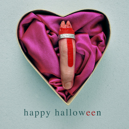 amputated: a scary amputated finger with a ring in a heart-shaped gift box, and the text happy halloween Stock Photo