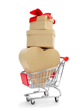 some heart-shaped gift boxes topped with a red ribbon in a shopping cart on a white background photo