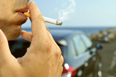 travelling salesman: closeup of a man with a burning cigarette in his mouth while is waiting besides a car parked next to a no traffic road Stock Photo