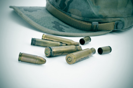 pointed arm: a camouflage cap and some bullets and bullet shells Stock Photo