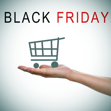 the text black friday and a man hand holding a shopping cart photo