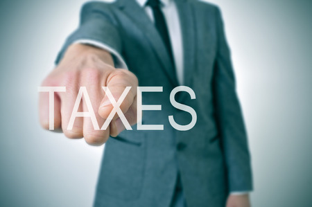 taxable: man wearing a suit pointing the finger to the word taxes written in the foreground Stock Photo