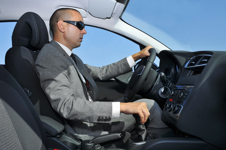 a young man wearing a suit and sunglasses driving a car with manual transmission photo