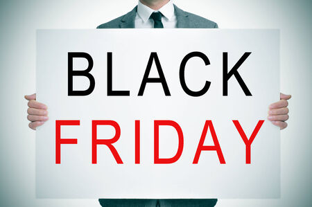 a man wearing a suit holding a signboard with the words black friday written in it photo