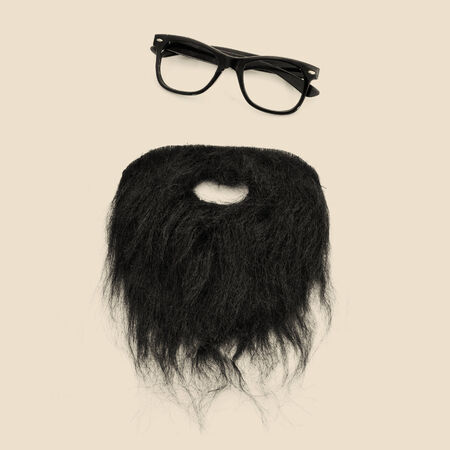 a pair of retro eyeglasses and a beard forming a man face on a beige background photo