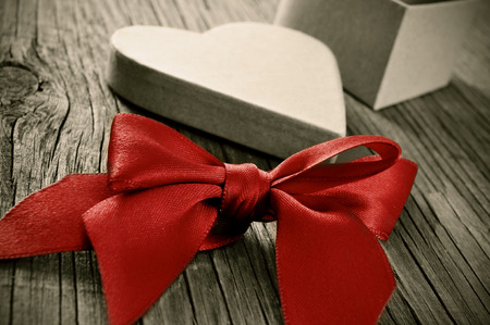 a red ribbon bow and a heart-shaped gift box on a weathered wooden table, with a retro effect photo