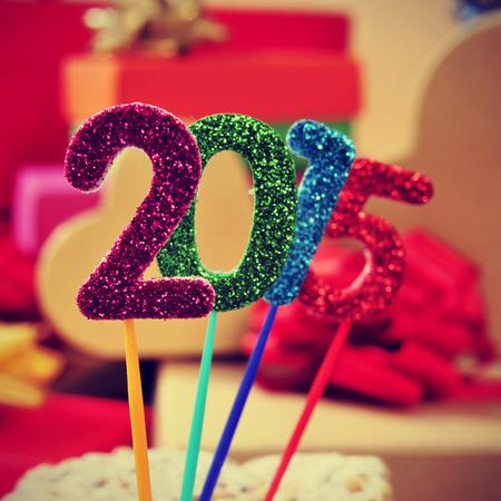 numbers of different colors forming the number 2015, as the new year, with a pile of gifts in the background photo