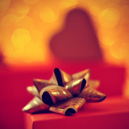 ribbon bow: closeup of a red gift box with a golden ribbon bow and some gifts in the background Stock Photo