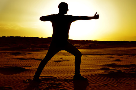 a young man practicing the yoga archer pose in backlight at sunset photo